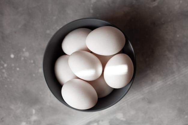 Talerz wypełniony jajkami, więcej niż cztery jajka, zdjęcie zrobione na betonowym tle. szary talerz i kurze jaja, promienie słoneczne wpadają w ramę.