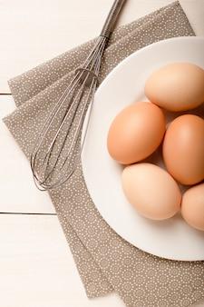 Talerz z brązowymi jajkami i trzepaczką na białym stole, składniki do gotowania, widok z góry