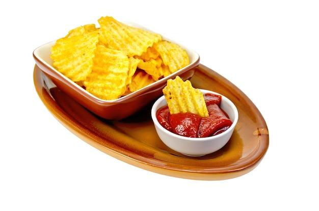 Talerz z chipsami ziemniaczanymi, miska z keczupem i frytkami na ceramice na białym tle