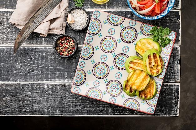 Talerz z cukinią i pustym miejscem, sałatka z pomidorów z cebulą i przyprawami na czarnym tle, widok z góry. koncepcja kuchni orientalnej