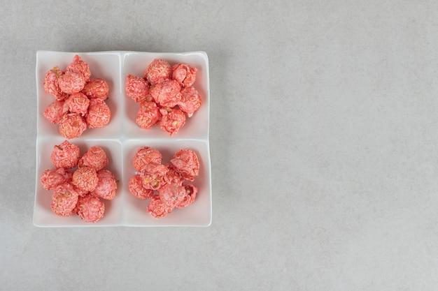 Talerz z czterema porcjami popcornu pokrytego cukierkami na marmurze.
