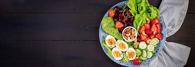 Talerz z dietą paleo. jajka na twardo, awokado, ogórek, orzechy, wiśnia i truskawki. śniadanie paleo. widok z góry