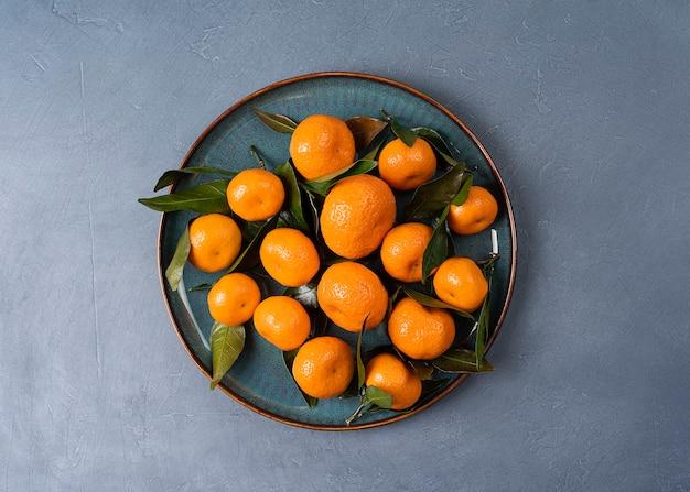 Talerz z dojrzałymi mandarynkami z liśćmi w wysokiej rozdzielczości