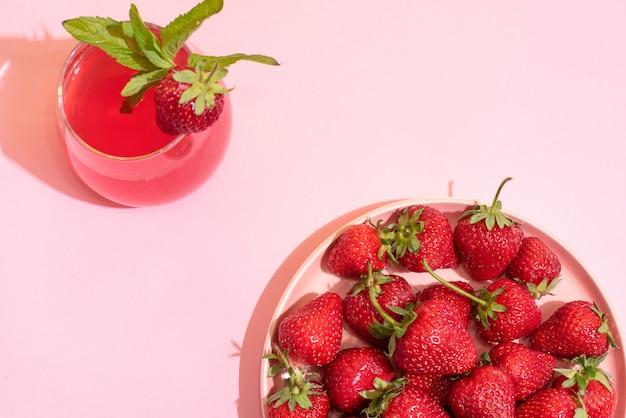 Talerz z dojrzałymi truskawkami i szklanką lemoniady truskawkowej na różowym tle, widok z góry, koncepcja lato, zbliżenie.