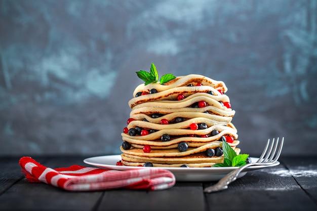 Talerz z domowymi pieczonymi naleśnikami ze świeżymi jagodami i miętą na pyszną przekąskę.