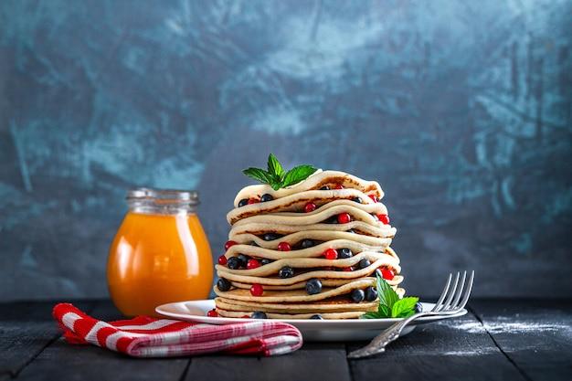 Talerz z domowymi pieczonymi naleśnikami ze świeżymi jagodami i słoik dżemu na pyszne śniadanie