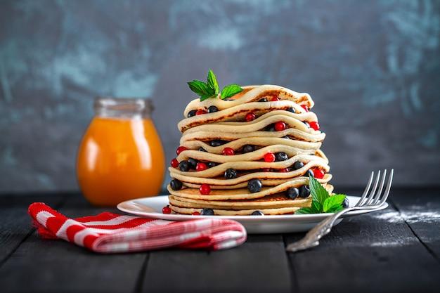 Talerz z domowymi pieczonymi naleśnikami ze świeżymi jagodami i słoik miodu na pyszne śniadanie