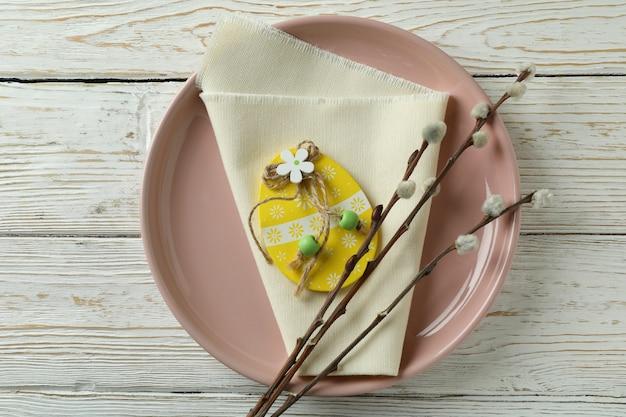 Talerz z drewnianą pisanką, serwetką kuchenną i baziami na drewnianym stole
