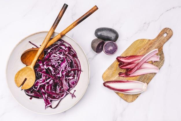 Talerz z fioletową czerwoną kapustą i fioletowymi ziemniakami drewnianą łyżką i fioletową cykorią na fioletowej desce do krojenia