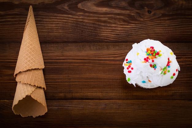 Talerz z gałką lodów waniliowych swith kropi i rożki waflowe na drewniane tła z miejsca kopiowania.