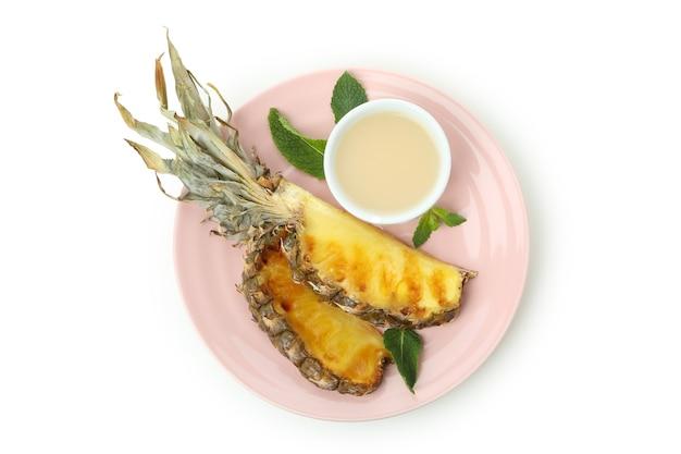 Talerz z grillowanym ananasem i sosem na białym tle.
