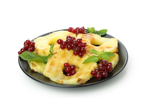 Talerz z grillowanym ananasem i żurawiną na białym tle.