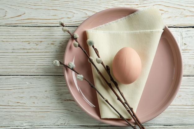 Talerz z jajkiem, serwetką kuchenną i baziami na drewnianym stole