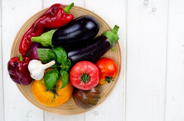 Talerz z jasnymi dojrzałymi warzywami na białym drewnianym stole. zdjęcie studyjne.