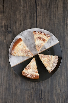 Talerz z kawałkami pysznego ciasta na drewnianym stole.