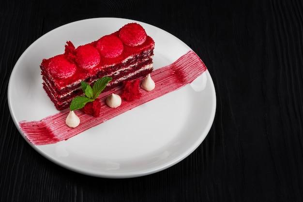 Talerz z kawałkiem pysznego czerwonego aksamitnego ciasta na czarnym drewnianym tle koncepcji jedzenia i picia