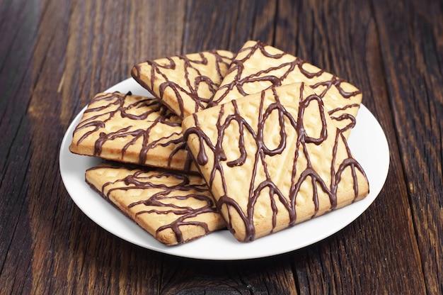 Talerz z kwadratowymi czekoladowymi ciasteczkami na ciemnym drewnianym stole