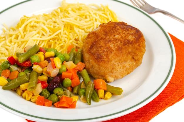 Talerz z makaronem, warzywami i kotletem panierowanym