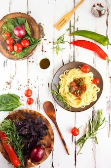 Talerz z makaronem. wiśnia, chili, pomidor, bazylia, przyprawy, estragon, cebula