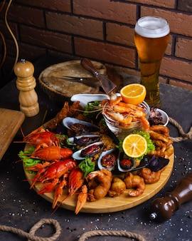 Talerz z owocami morza z krewetkami, małżami, homarami podawany z cytryną i szklanką piwa