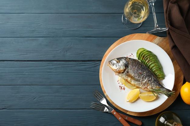Talerz z piec dorado ryba na garnirującym drewnianym tle, odgórny widok