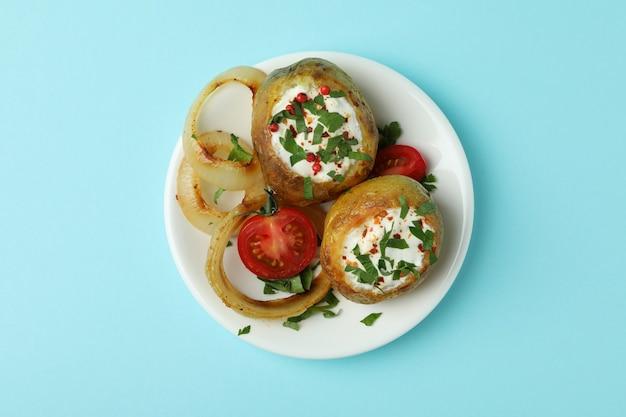 Talerz z pieczonym ziemniakiem na niebieskim tle.