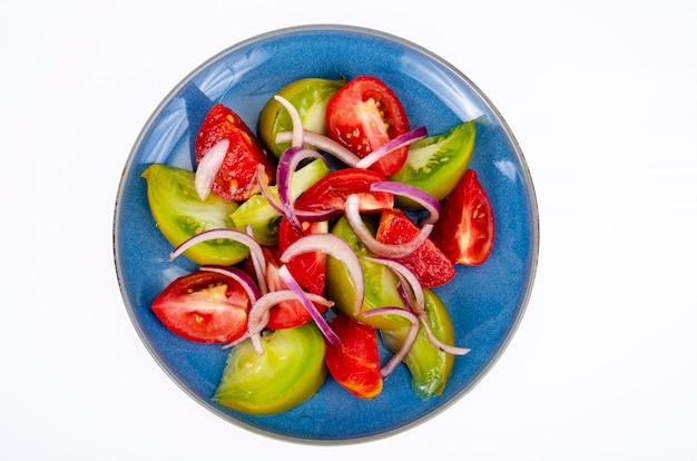 Talerz z plastrami dojrzałych pomidorów w różnych kolorach. zdjęcie studyjne.