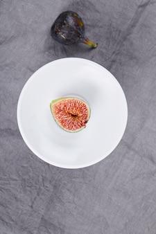 Talerz z plastrami figi i całą czarną figą na szarym tle. wysokiej jakości zdjęcie