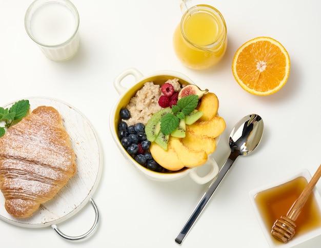 Talerz z płatkami owsianymi i owocami, pół dojrzałej pomarańczy i świeżo wyciśnięty sok w przezroczystej szklanej karafce, miód w misce na białym stole. zdrowe śniadanie