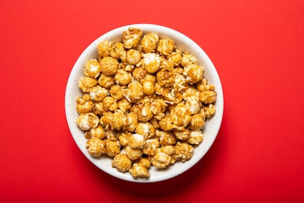 Talerz z popcornem karmelowym na czerwonym tle