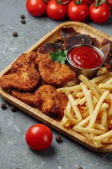 Talerz z przekąskami. panierowane nuggetsy z kurczaka, smażone ziemniaki i jamon.