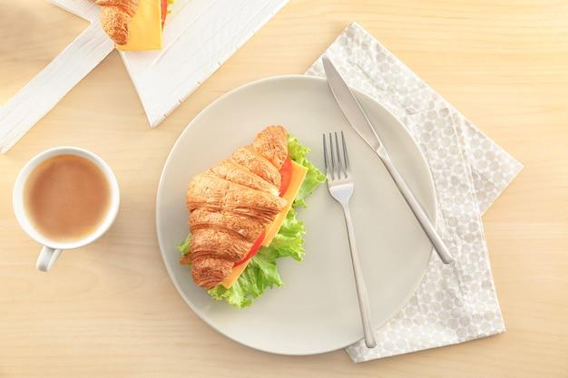 Talerz z pyszną kanapką z rogalikiem na stole