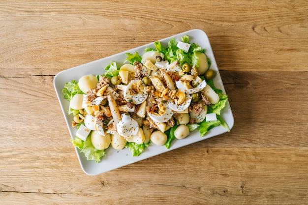 Talerz z pyszną sałatką z sałaty, ziemniaków, sera i orzechów na drewnianym stole. koncepcja zdrowego stylu życia