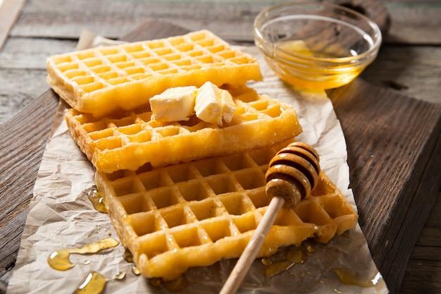 Talerz z pysznym miodem waflowym i plasterkiem masła. na drewnianym tle. zbliżenie