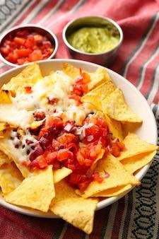Talerz z pysznymi nachos, serem, mięsem mielonym i salsą na stole