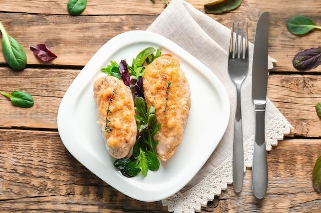 Talerz z pysznymi piersiami z kurczaka na drewnianym stole