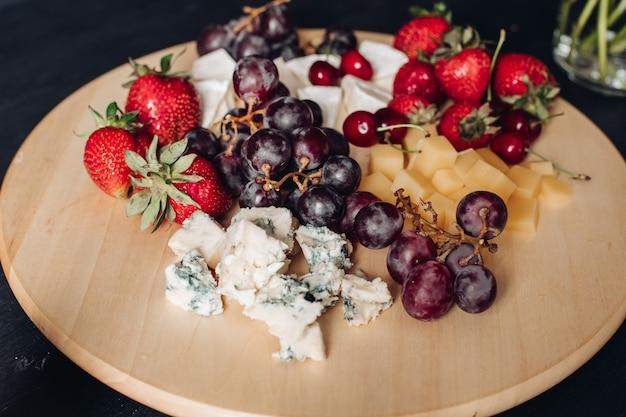 Talerz z różnorodnymi owocami i serem. zbliżenie na pyszny talerz z jedzeniem