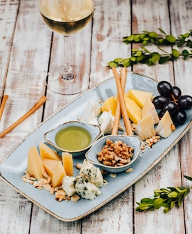 Talerz z różnymi serami i winogronami oraz kieliszek do białego wina