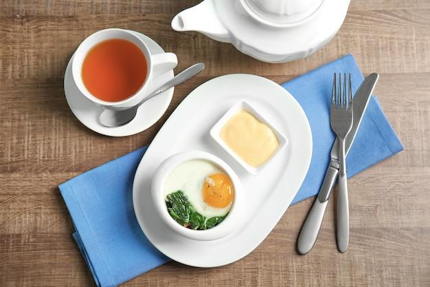 Talerz z smacznym jajkiem i szpinakiem na drewnianym stole