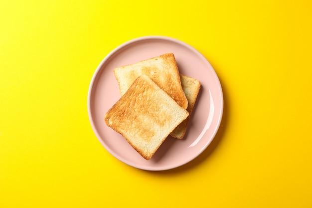 Talerz z smakowitymi grzankami na żółtym tle, odgórny widok