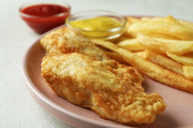 Talerz z smażoną rybą i frytkami i sosami na białym tle z teksturą