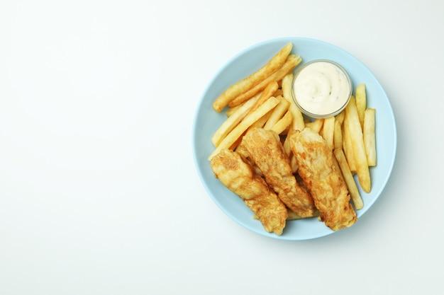 Talerz z smażoną rybą z frytkami i sosem na białym tle