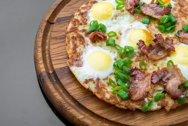 Talerz z smażonymi jajkami, bekonem, pomidorem i plackami ziemniaczanymi z bliska