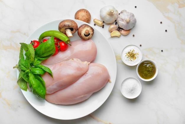 Talerz z surowym filetem z kurczaka, ziołami i warzywami na stole