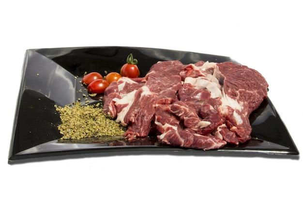 Talerz z surowym mięsem i dekoracjami jedzenia wokół na białym tle, izolowany obiekt