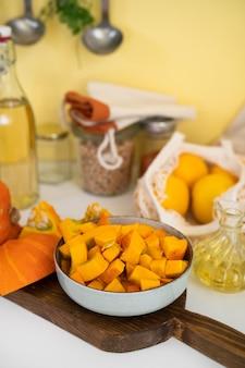 Talerz z surowymi kawałkami dyni na stole kuchennym. pozytywny żółty backgorund. koncepcja jesień. święto dziękczynienia