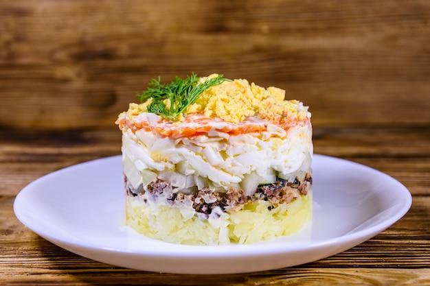 Talerz z tradycyjną rosyjską sałatką mimosa na drewnianym stole. sałatka warstwowa z ziemniakami, sardynką, serem, marchewką, jajkiem i majonezem