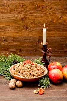 Talerz z tradycyjnym bożonarodzeniowym poczęstunkiem słowian w wigilię. gałąź świerkowa, jabłka i świeca na drewnianym tle