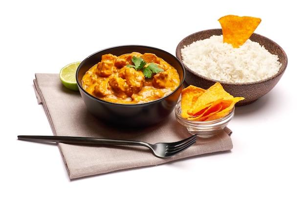 Talerz z tradycyjnym curry z kurczaka i nachos na białym tle