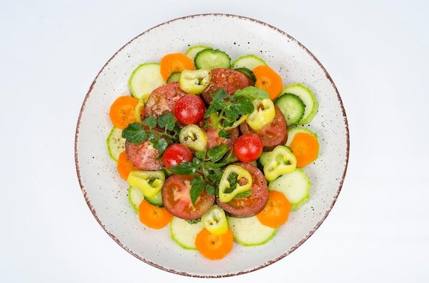 Talerz z warzywami na białym tle. jedzenie wegetariańskie. zdjęcie studyjne.